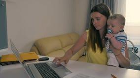 La madre joven trabaja en el ordenador portátil con el bebé en manos metrajes