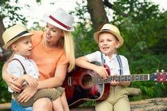 La madre joven y dos hijos están descansando en el bosque, cantando canciones con una guitarra fotos de archivo
