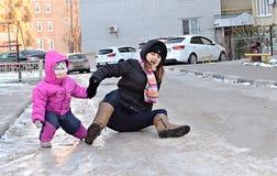 La madre joven y el bebé se cayeron en la calle esmaltada de la helada Imágenes de archivo libres de regalías
