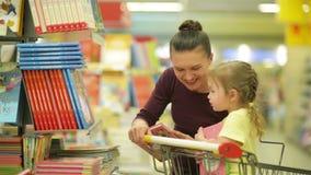 La madre joven y la hija adorable en niños selectos del carro de la compra reserva en supermercado almacen de metraje de vídeo
