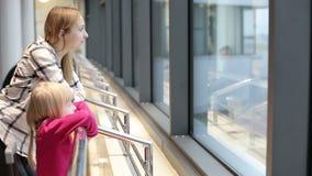 La madre joven y la pequeña hija están mirando a través de la ventana en el aeropuerto almacen de video