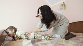 La madre joven y la muchacha adorable engaña alrededor en casa en la cama almacen de metraje de vídeo