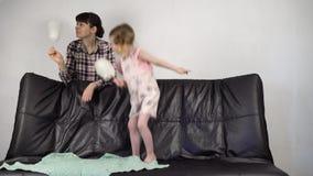 La madre joven y la pequeña hija dulce juntas comen el caramelo de algodón en casa almacen de video