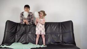 La madre joven y la pequeña hija dulce juntas comen el caramelo de algodón en casa almacen de metraje de vídeo