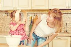 La madre joven y pequeña la hija linda que preparan la pasta, cuecen las galletas y la diversión el tener en la cocina Foto de archivo