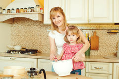 La madre joven y pequeña la hija linda que preparan la pasta, cuecen las galletas y la diversión el tener en la cocina Foto de archivo libre de regalías