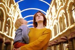 La madre joven y su pequeño hijo disfrutan de la iluminación hermosa de la ciudad Fotos de archivo