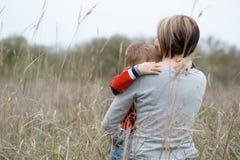 La madre joven y su pequeño hijo se abrazan con gusto Imagen de archivo