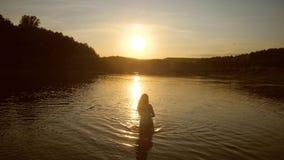 La madre juega con el bebé en sus brazos, madre y el niño se baña en el río contra la puesta del sol, cámara lenta