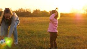 la madre juega con poca hija en bola C?mara lenta El ni?o feliz corre con la bola en hierba, lanza el bal?n de f?tbol Familia almacen de video