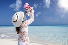 La madre juega con su hija del bebé en la playa tropical fotos de archivo libres de regalías