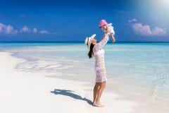 La madre juega con su hija del bebé en una playa en los Maldivas fotos de archivo