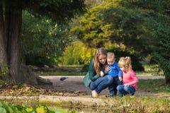 La madre juega con su hija e hijo en el parque por la charca foto de archivo