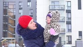 La madre juguetona con el bebé disfruta de la ventisca de la caída de la nieve en yarda de la casa 4K metrajes