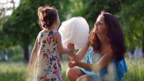 la madre 4K y el niño en el parque están comiendo la seda del caramelo almacen de video