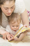 La madre lee el libro al bebé. Fotos de archivo libres de regalías