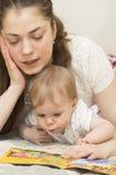 La madre lee el libro al bebé. Fotografía de archivo libre de regalías