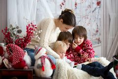 La madre lee el libro a sus hijos, niños que se sientan en butaca acogedora en un día de invierno nevoso foto de archivo libre de regalías