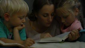 La madre lee un cuento para los niños almacen de video