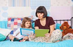 La madre lee un libro interesante a su pequeña hija imagenes de archivo