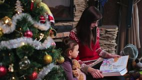 La madre lee un libro para su hija cerca del árbol de navidad metrajes