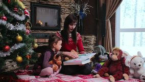La madre lee un libro para su hija cerca del árbol de navidad almacen de video