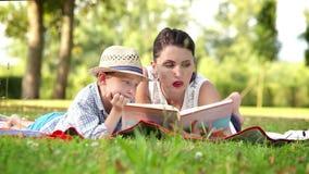 La madre lee un libro a su hijo mientras que en la comida campestre en el parque almacen de metraje de vídeo