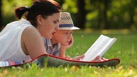 La madre lee un libro a su hijo mientras que en la comida campestre en el parque almacen de video