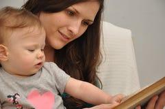La madre lee un libro a una hija del bebé Fotos de archivo