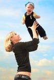 La madre levanta al niño en las manos al aire libre Fotografía de archivo libre de regalías