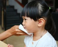 La madre limpia la boca del bebé con el papel seda imágenes de archivo libres de regalías