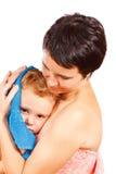 La madre limpia la cabeza a su hijo después de bañar Imagenes de archivo