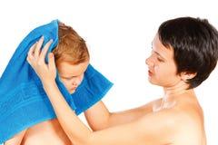 La madre limpia la cabeza a su hijo después de bañar Fotografía de archivo