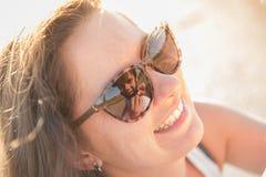 La madre linda feliz ayuda al niño sonriente a llevar el casco en la reflexión de las gafas de sol Imagenes de archivo