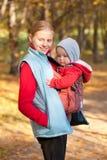La madre lleva al bebé del niño en parque Imagen de archivo libre de regalías