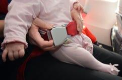 La madre lleva a su bebé infantil durante vuelo imagen de archivo