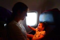 La madre lleva a su bebé infantil durante vuelo Fotografía de archivo