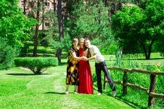La madre mayor feliz con la hija adulta y el hijo caminan en jardín hermoso del verano fotos de archivo libres de regalías