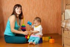 La madre mette il bambino su banale Immagini Stock