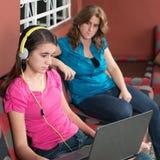 La madre mira a su hija adolescente enviciada Internet Foto de archivo libre de regalías