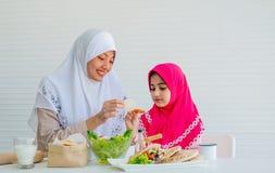 La madre musulmana ha azione per la motivazione di sua figlia per mangiare i pomodori di verdure e particolarmente freschi per i  immagine stock libera da diritti