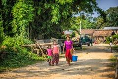 La madre nepalese con due bambini cammina attraverso il loro villaggio Fotografia Stock