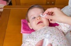 La madre passa gli occhi di pulizia del bambino con cotone Fotografia Stock