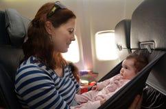 La madre porta il suo bambino infantile durante il volo Fotografia Stock