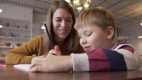La madre positiva comunica con su hijo joven durante actividades de desarrollo metrajes