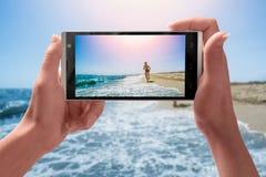 La madre prende un'immagine di suo figlio su una spiaggia fotografia stock libera da diritti