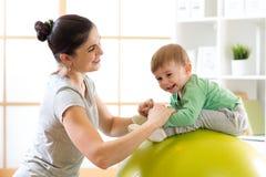 La madre preoccupantesi che fa lo sport si esercita con il suo bambino su fitball Fotografie Stock
