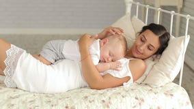 La madre preoccupantesi delicata tiene il suo neonato addormentato nelle sue armi stock footage