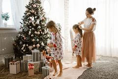 La madre preoccupantesi intreccia la treccia della sua piccola figlia mentre la figlia di secondo decora l'albero di un nuovo ann fotografia stock libera da diritti