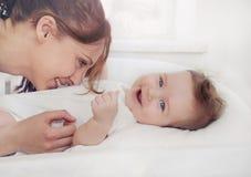 La madre preoccupantesi ride con il suo neonato felice sveglio Fotografia Stock
